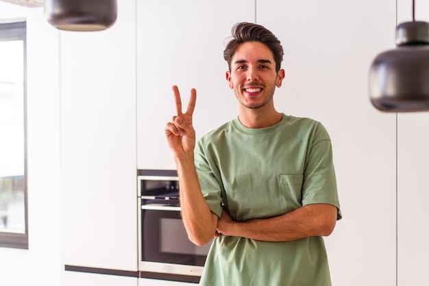 Молодой человек смешанной расы в своей кухне показывает номер два пальцами.