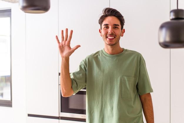 Молодой человек смешанной расы в своей кухне улыбается веселый, показывая номер пять с пальцами.