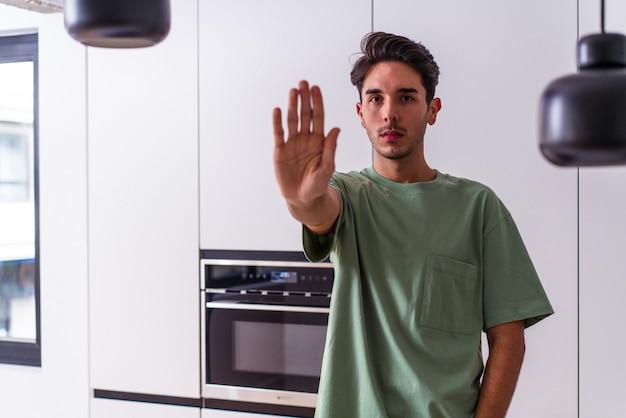 Молодой человек смешанной расы в своей кухне, стоя с протянутой рукой, показывая знак остановки, предотвращая вас.
