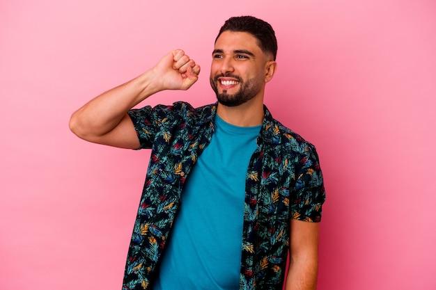 勝利、情熱と熱意、幸せな表現を祝うピンクの背景に分離された若い混血の男。