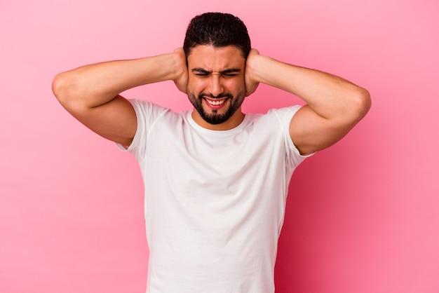 ピンクの背景に孤立した若い混血の男性が、大きすぎる音を聞かないように手で耳を覆っています。