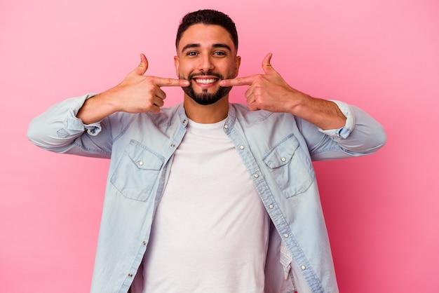 ピンクの背景の笑顔で孤立した若い混血の男は、口に指を指しています。