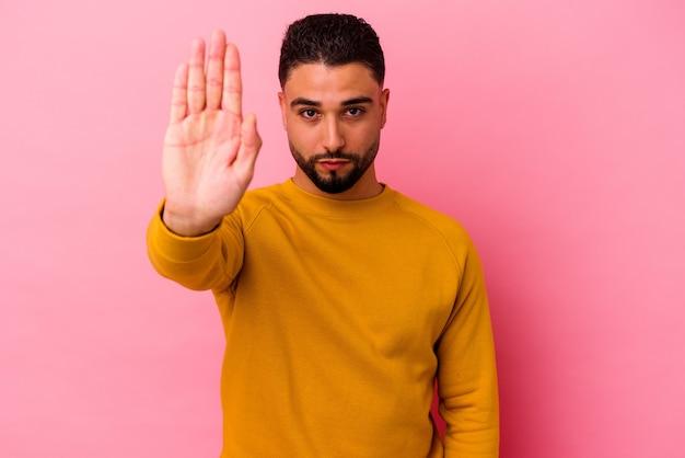 Молодой человек смешанной расы изолирован на розовой стене, стоящей с протянутой рукой, показывая знак остановки, предотвращая вас.