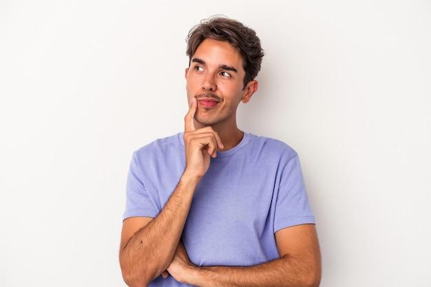 考え、戦略を計画し、ビジネスの方法を考えて、白い背景に孤立した若い混血の男。