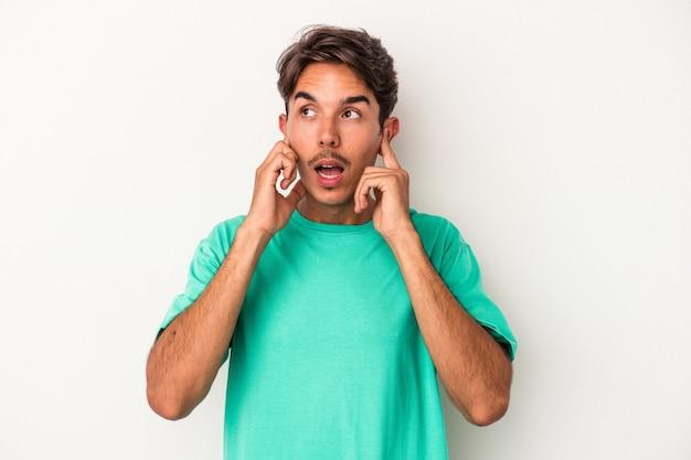 指で耳を覆っている白い背景に孤立した若い混血の男は、大声で周囲によってストレスと必死になりました。