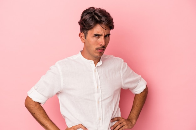 흰색 배경에 격리된 젊은 혼혈 남자는 불쾌한 표정으로 얼굴을 찌푸리고 팔짱을 끼고 있습니다.