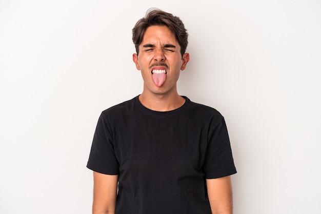 面白いとフレンドリーな舌を突き出して白い背景で隔離の若い混血の男。
