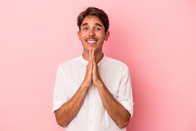 口の近くで祈って手をつないで白い背景で隔離の若い混血の男は、自信を持っています。