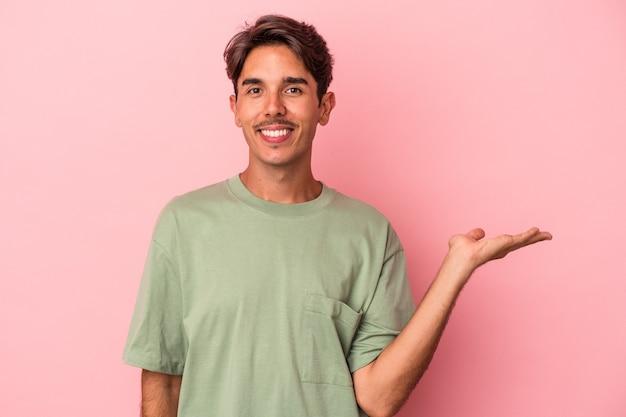 手のひらにコピースペースを示し、腰に別の手を保持している白い背景で隔離の若い混血人。