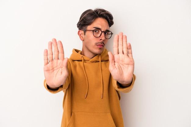一時停止の標識を示す伸ばした手で立っている白い背景で隔離の若い混血の男は、あなたを防ぎます。