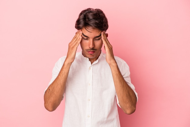 寺院に触れて頭痛を持っている白い背景で隔離の若い混血の男。