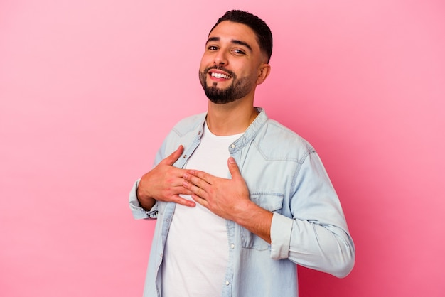 Young mixed race man isolated on pink background has friendly expression, pressing palm to chest. love concept.