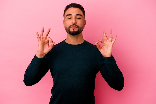 Young mixed race man isolated on pink background relaxes after hard working day, she is performing yoga.