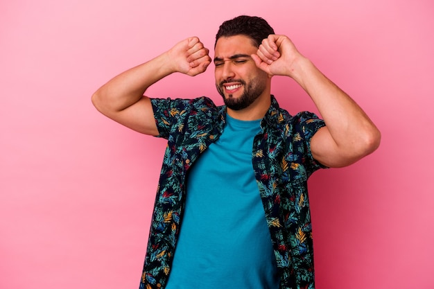 Young mixed race man isolated on pink wall celebrating a special day, jumps and raise arms with energy.