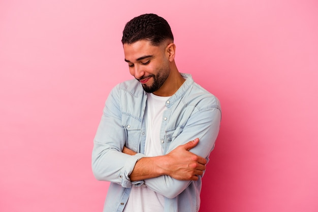 Young mixed race man isolated on pink wall hugs, smiling carefree and happy.
