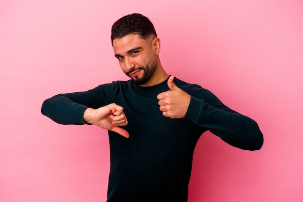Young mixed race man isolated on pink wall showing thumbs up and thumbs down, difficult choose concept