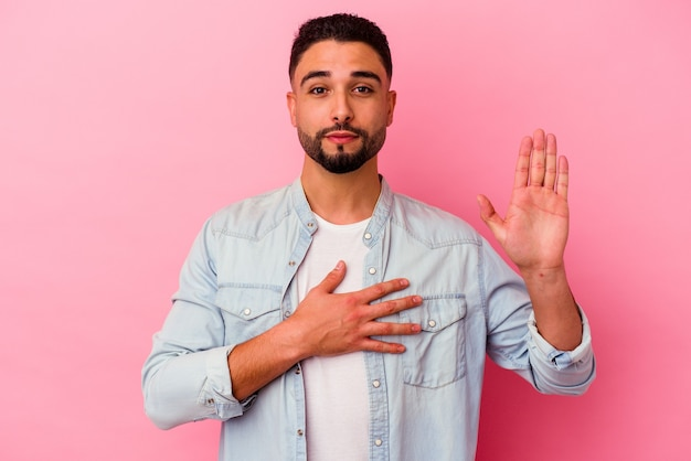Young mixed race man isolated on pink wall taking an oath, putting hand on chest.