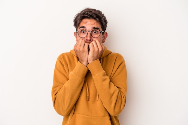 Young mixed race man isolated on white background biting fingernails, nervous and very anxious.