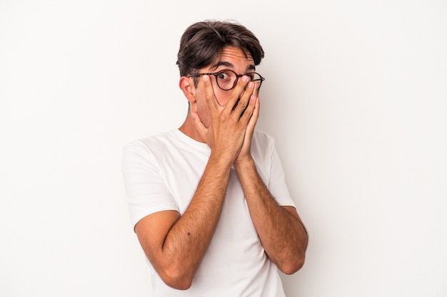 Young mixed race man isolated on white background blink through fingers frightened and nervous.