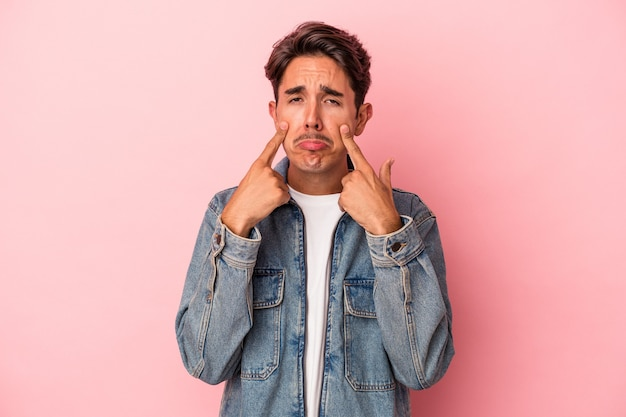 Young mixed race man isolated on white background crying, unhappy with something, agony and confusion concept.