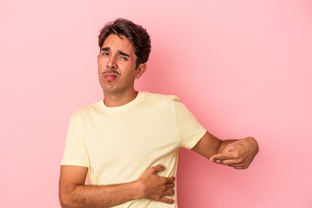 Young mixed race man isolated on white background having a liver pain, stomach ache.
