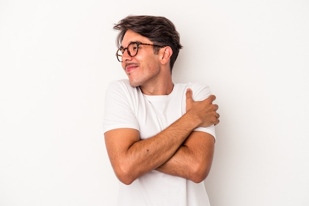 Young mixed race man isolated on white background hugs, smiling carefree and happy.
