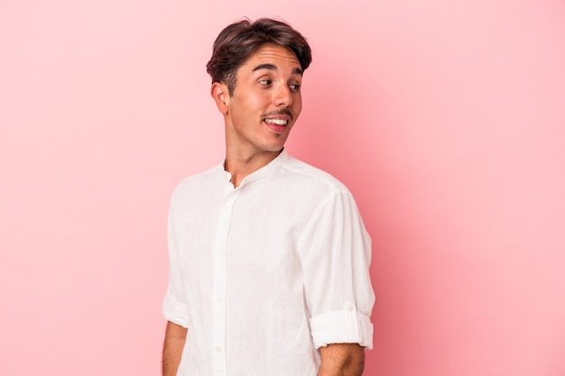 Young mixed race man isolated on white background looks aside smiling, cheerful and pleasant.