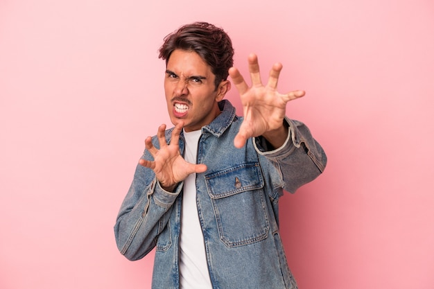 Young mixed race man isolated on white background showing claws imitating a cat, aggressive gesture.