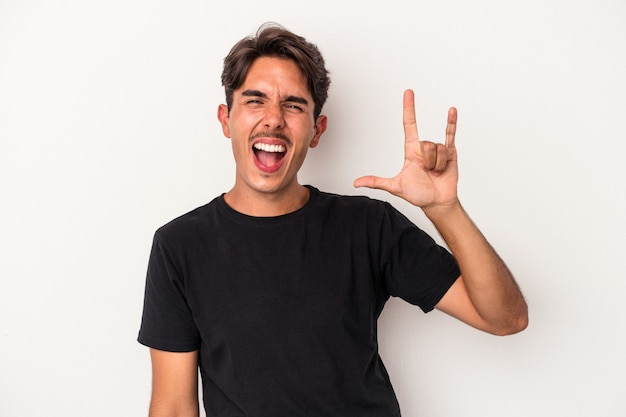 Young mixed race man isolated on white background showing a horns gesture as a revolution concept.