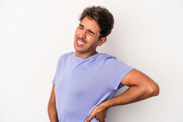 Young mixed race man isolated on white background suffering a back pain.