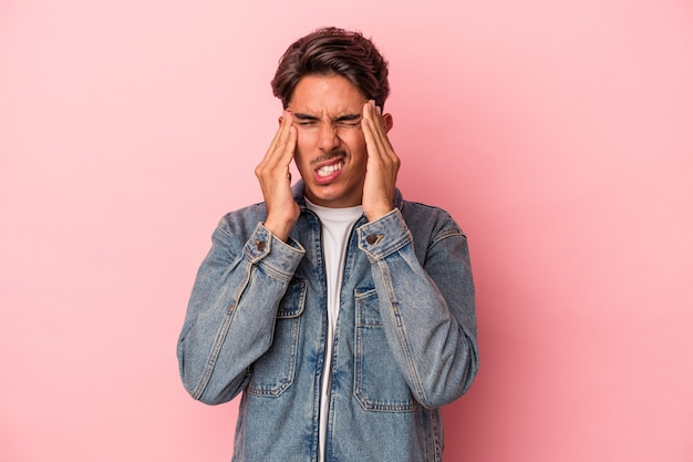 Young mixed race man isolated on white background touching temples and having headache.