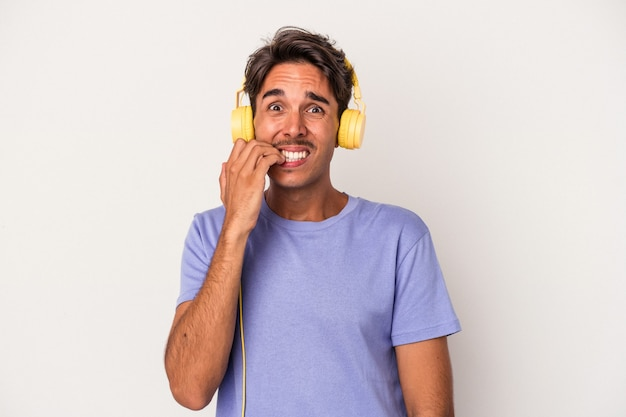 Young mixed race man listening to music isolated on blue background biting fingernails, nervous and very anxious.