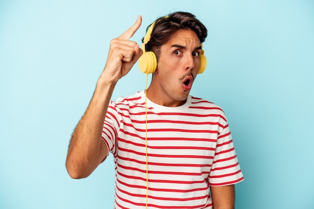 Young mixed race man listening to music isolated on blue background having an idea, inspiration concept.