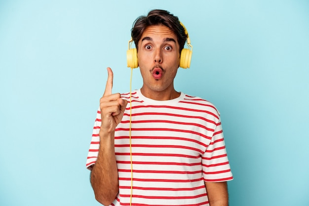 Young mixed race man listening to music isolated on blue background having some great idea, concept of creativity.