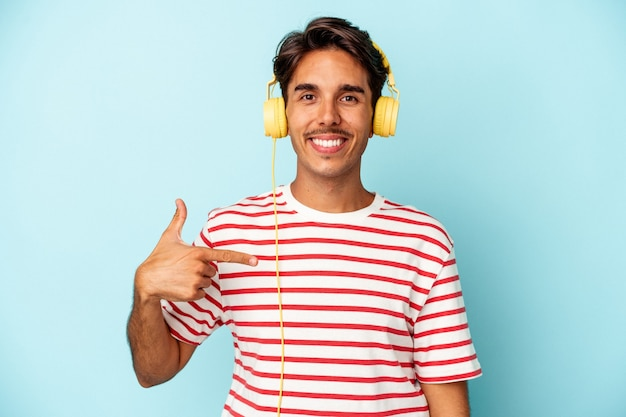 Young mixed race man listening to music isolated on blue background person pointing by hand to a shirt copy space, proud and confident