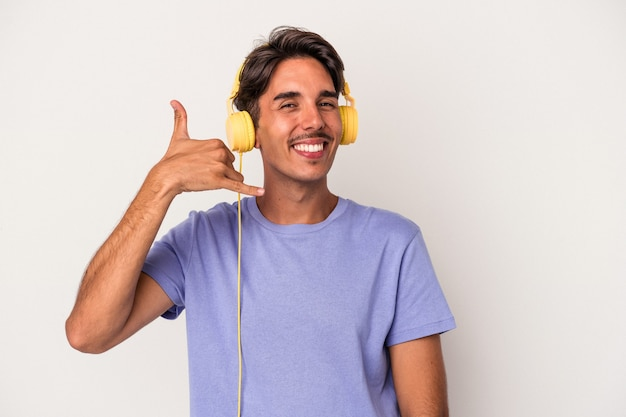 Young mixed race man listening to music isolated on blue background showing a mobile phone call gesture with fingers.