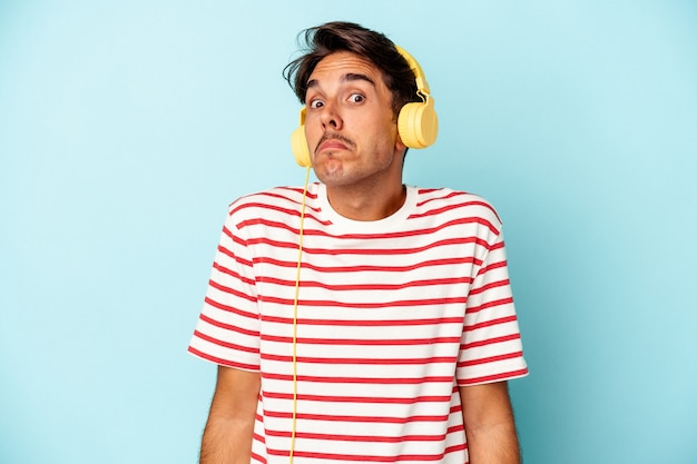 Young mixed race man listening to music isolated on blue background shrugs shoulders and open eyes confused.