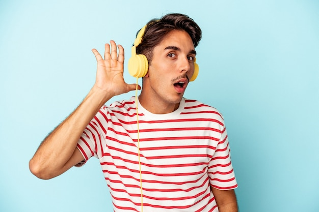 Young mixed race man listening to music isolated on blue background trying to listening a gossip.