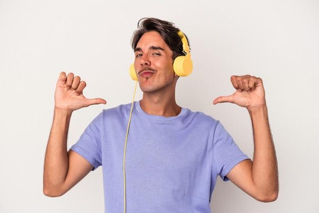 青い背景で隔離された音楽を聞いている若い混血の男は、誇りと自信を持って、従うべき例を感じます。