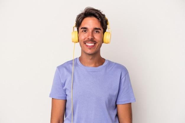 幸せ、笑顔、陽気な青い背景で隔離の音楽を聴いている若い混血の男。