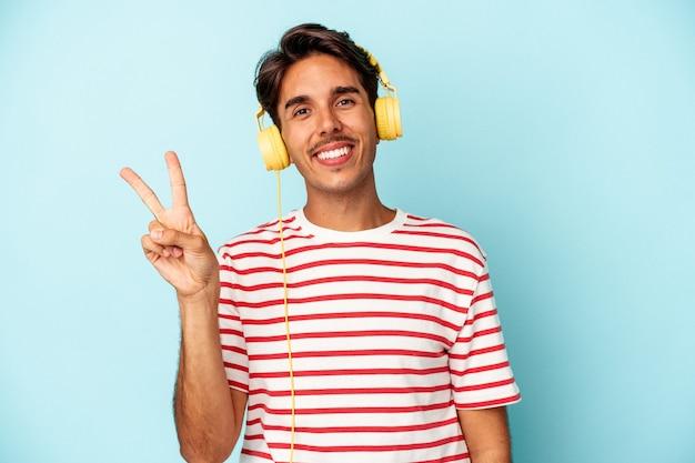 青い背景に分離された音楽を聞いている若い混血の男は、指で平和のシンボルを示して楽しくてのんきです。