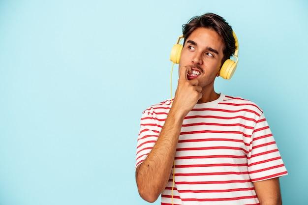 青い背景に分離された音楽を聞いている若い混血の男は、コピースペースを見ている何かについて考えてリラックスしました。