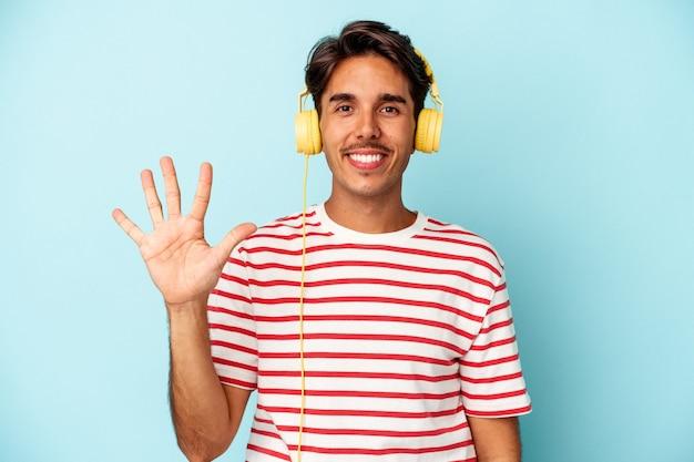 青い背景に分離された音楽を聞いている若い混血の男は、指で5番を示して陽気に笑っています。