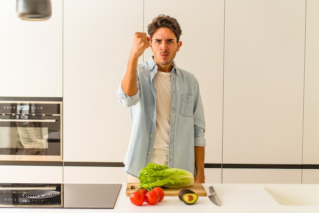 カメラに拳、攻撃的な表情を示す昼食のためのサラダを準備している若い混血の男。