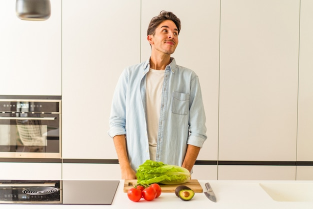 Young mixed race man preparing a salad for lunch dreaming of achieving goals and purposes