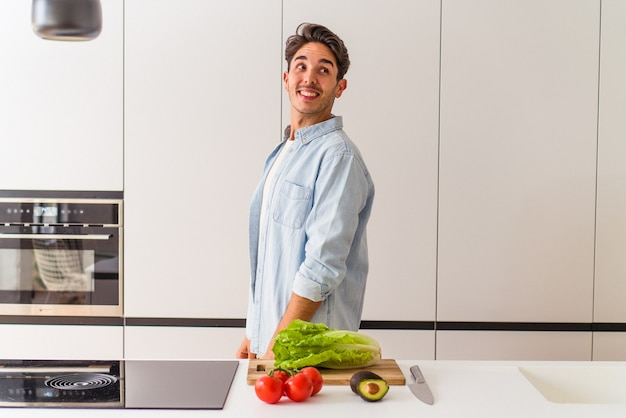 Young mixed race man preparing a salad for lunch looks aside smiling, cheerful and pleasant.