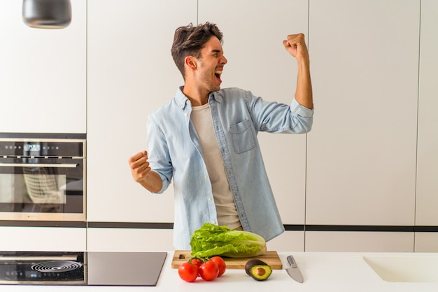 Young mixed race man preparing a salad for lunch raising fist after a victory, winner concept.