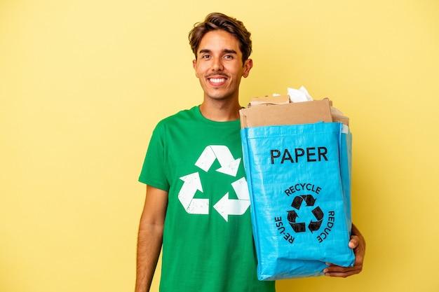 Молодой человек смешанной расы, рециркулирующий бумагу, изолированную на желтом фоне, счастлив, улыбчив и весел.