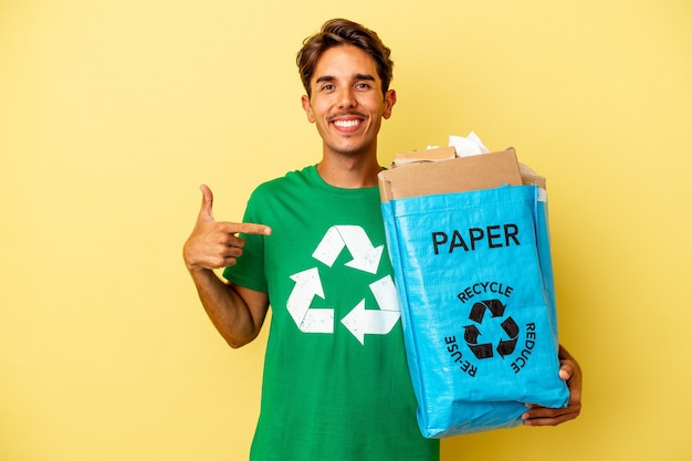 Young mixed race man recycling paper isolated on yellow background person pointing by hand to a shirt copy space, proud and confident