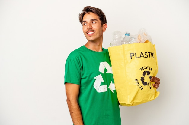 Young mixed race man recycling plastic isolated on yellow background looks aside smiling, cheerful and pleasant.